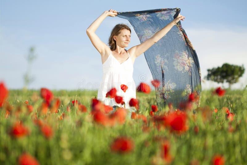 Κορίτσι που απολαμβάνει το καλοκαίρι σε έναν τομέα παπαρουνών στοκ εικόνες με δικαίωμα ελεύθερης χρήσης