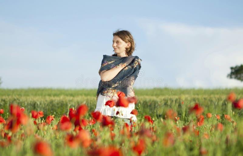 Κορίτσι που απολαμβάνει το καλοκαίρι σε έναν τομέα παπαρουνών στοκ φωτογραφίες