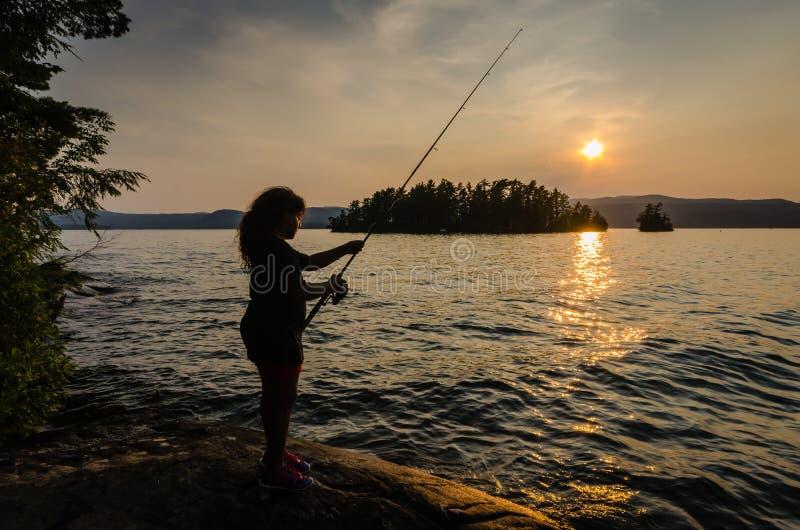 Κορίτσι που αλιεύει στο ηλιοβασίλεμα στοκ εικόνες