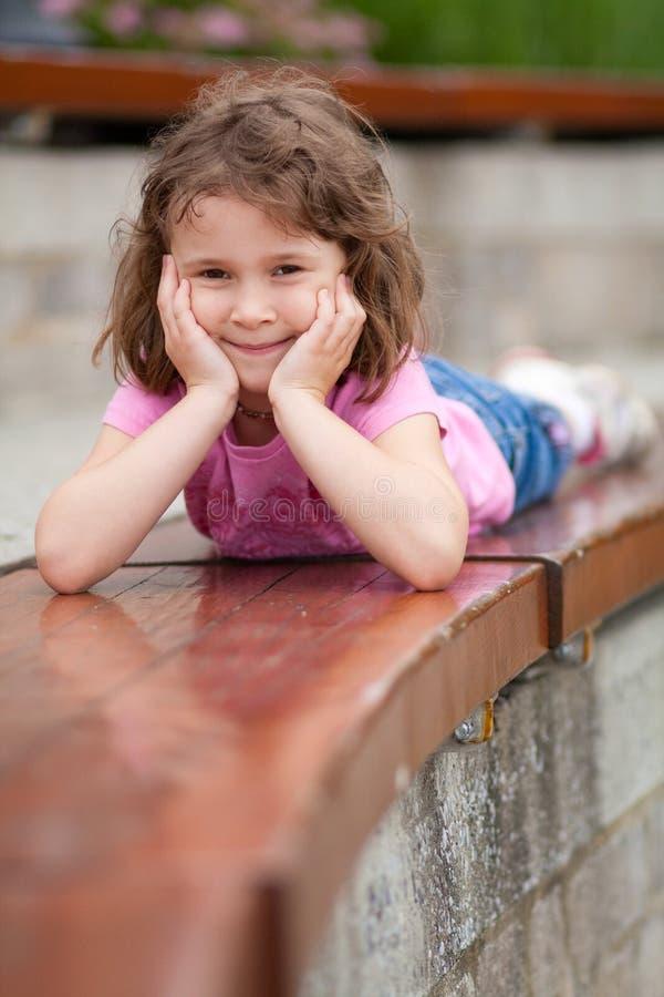 Κορίτσι που βάζει σε έναν πάγκο στοκ εικόνες