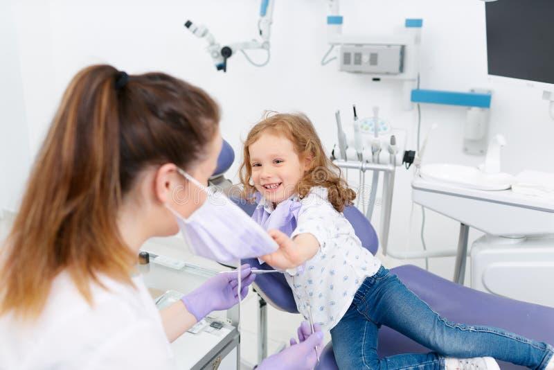Κορίτσι που βγάζει τον οδοντίατρο μορφής μασκών στοκ εικόνα