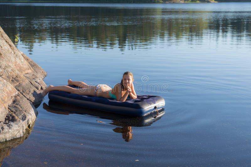 Κορίτσι που βρίσκεται σε ένα διογκώσιμο στρώμα στοκ φωτογραφία