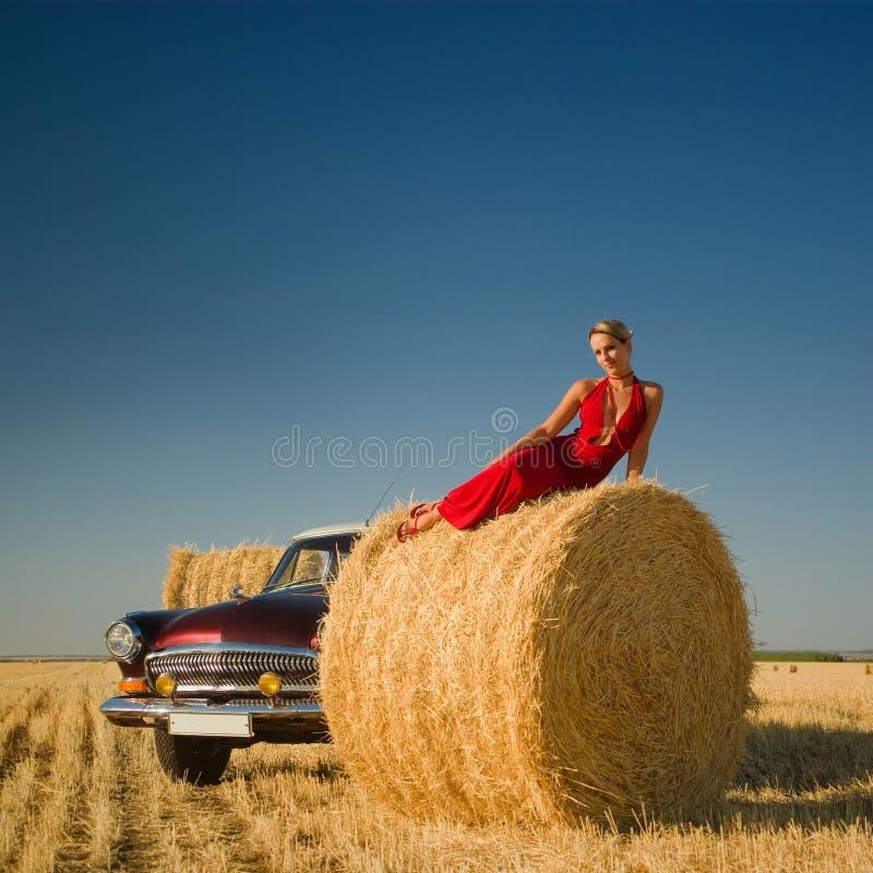 Κορίτσι που βρίσκεται στο δέμα αχύρου με το αναδρομικό υπόβαθρο αυτοκινήτων στοκ εικόνες με δικαίωμα ελεύθερης χρήσης