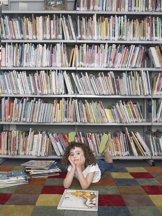 Κορίτσι που βρίσκεται στο πάτωμα με Storybook στη βιβλιοθήκη στοκ φωτογραφία
