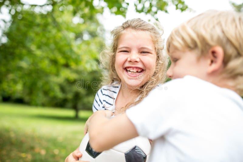 Κορίτσι που γελά κατά τη διάρκεια της διαμάχης με τον αδελφό στοκ εικόνες με δικαίωμα ελεύθερης χρήσης