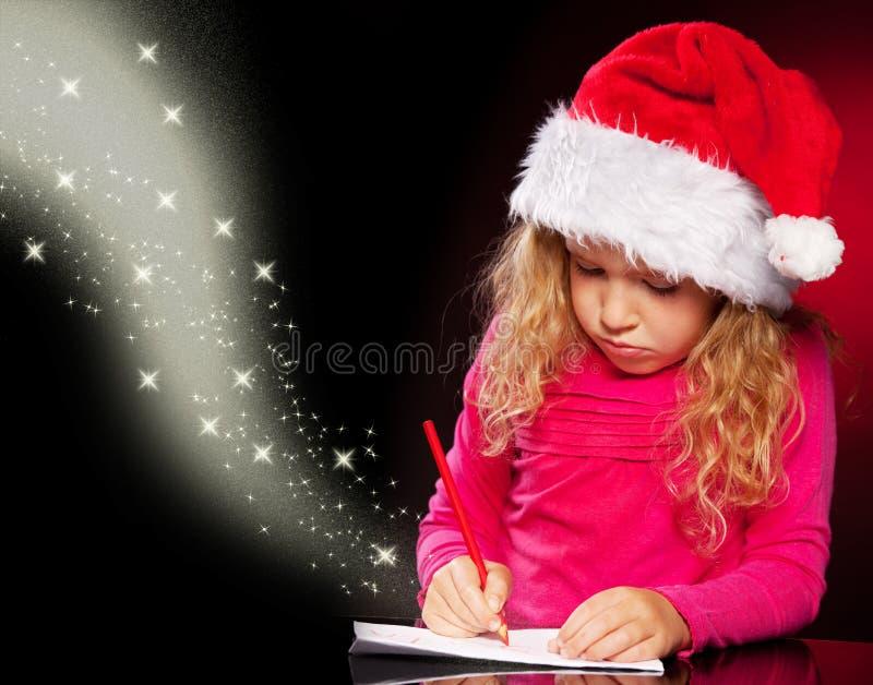 Κορίτσι που γράφει μια επιστολή σε Άγιο Βασίλη στοκ φωτογραφία