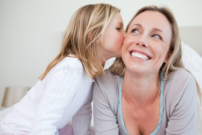 Κορίτσι που δίνει της τη μητέρα ένα φιλί στοκ φωτογραφία