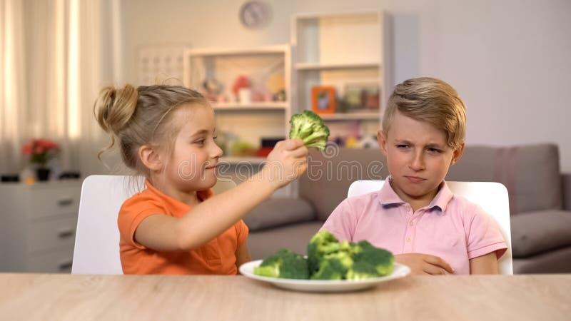 Κορίτσι που δίνει το μπρόκολο αδελφών, που παίζει με τα τρόφιμα, unappetizing υγιή τρόφιμα στοκ εικόνα