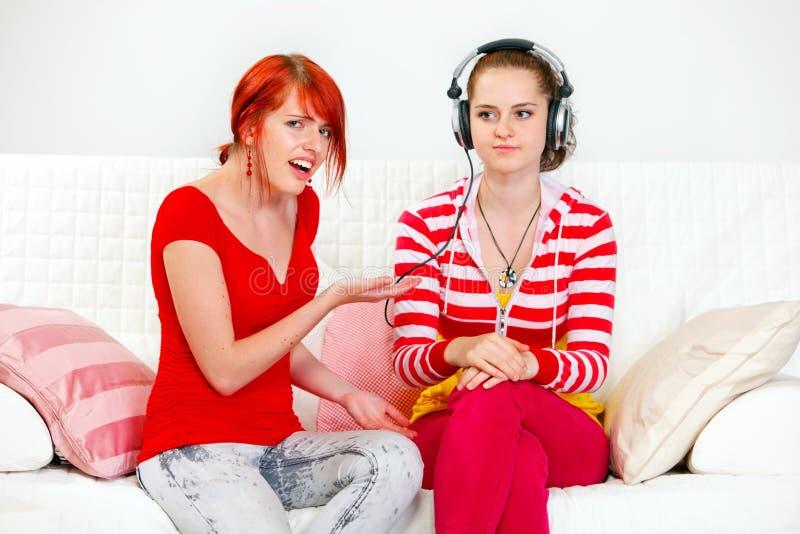 Κορίτσι που δείχνει στη μουσική ακούσματος φίλων της στοκ εικόνες