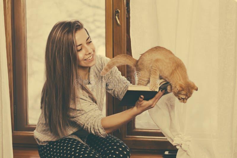 Κορίτσι που διαβάζει ένα βιβλίο και που παίζει με ένα γατάκι στοκ εικόνα