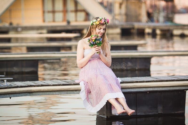 Κορίτσι που εγκαθιστά στην αποβάθρα στη λίμνη στοκ εικόνες