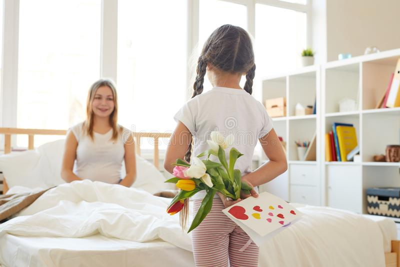 Κορίτσι που εκπλήσσει Mom με τα λουλούδια στοκ φωτογραφίες