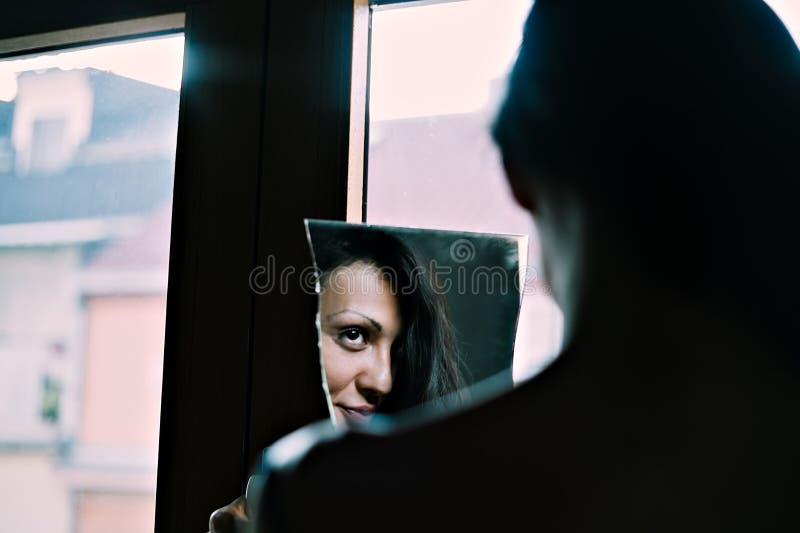 Κορίτσι που εξετάζει την αντανάκλαση σε έναν καθρέφτη στοκ εικόνες