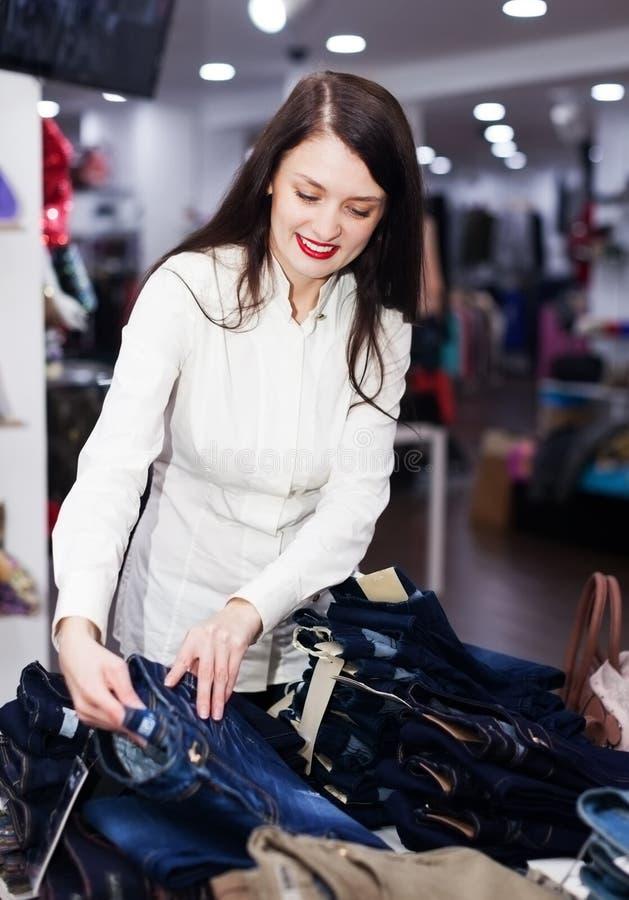Κορίτσι που επιλέγει το παντελόνι στο κατάστημα στοκ εικόνες
