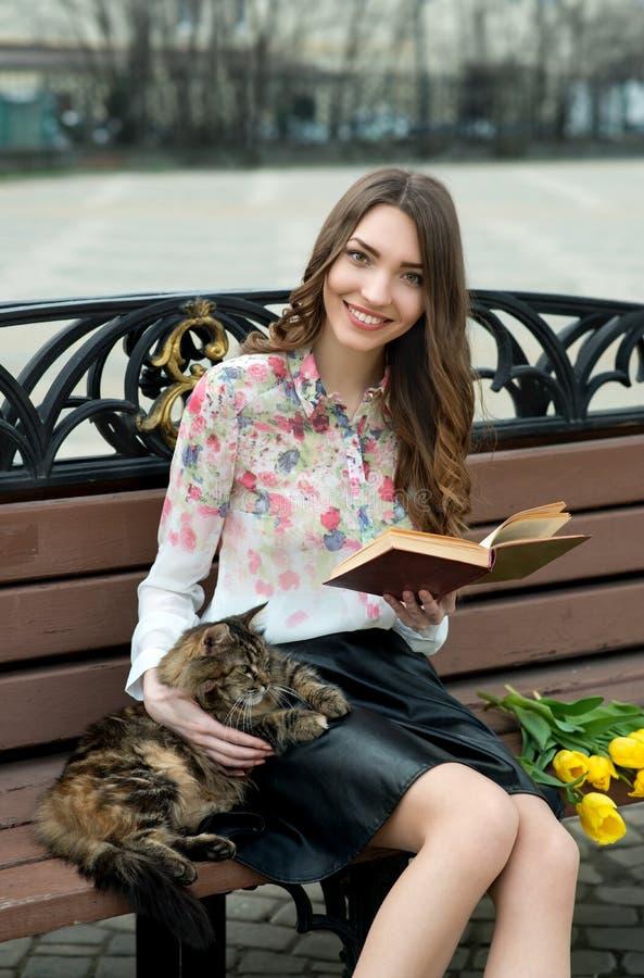 Κορίτσι που διαβάζει ένα βιβλίο με μια γάτα σε έναν πάγκο στην πόλη στοκ εικόνα