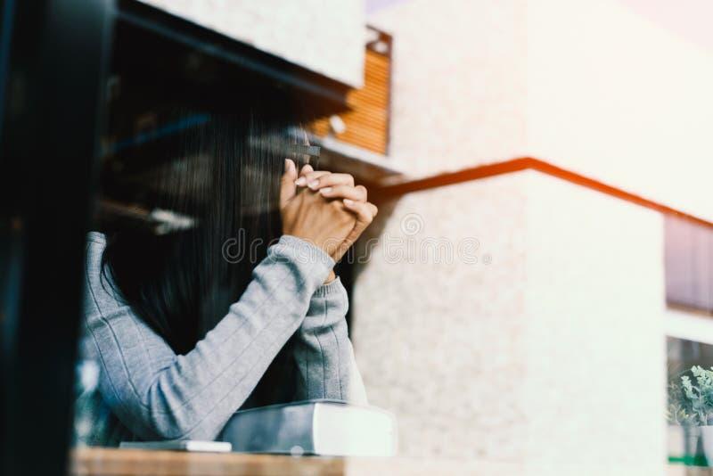 Κορίτσι που διαβάζει τη Βίβλο στον καφέ βιβλιοθηκών στοκ εικόνες