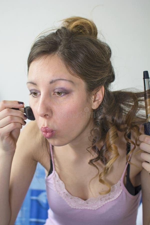 Κορίτσι που ισιώνει την τρίχα της και που βάζει στο makeup στοκ φωτογραφίες