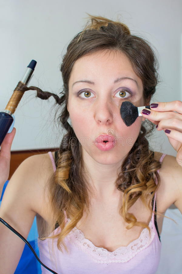 Κορίτσι που ισιώνει την τρίχα της και που βάζει στο makeup στοκ εικόνες