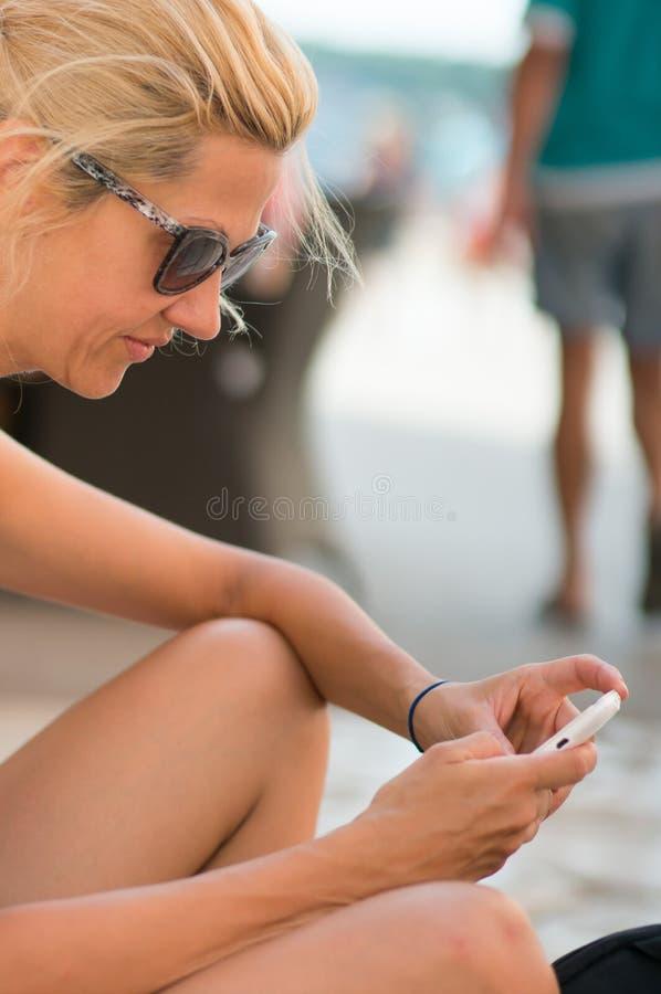 Κορίτσι που κάθεται και που στέλνει ένα μήνυμα κειμένου στοκ φωτογραφία