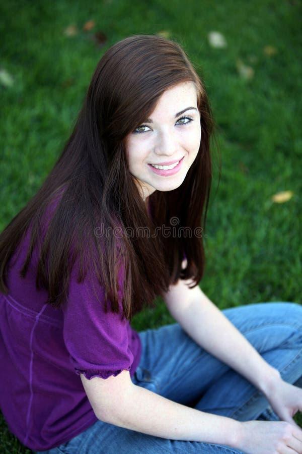 Κορίτσι που κάθεται στη χλόη στοκ εικόνες