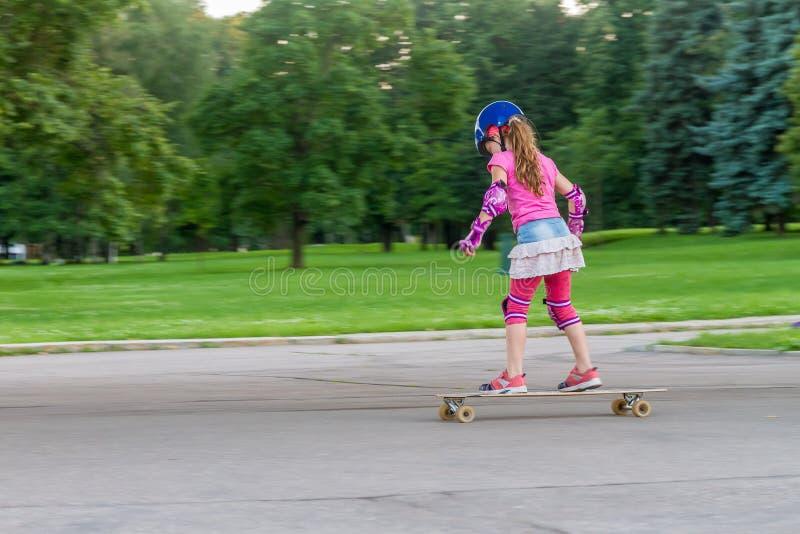 Κορίτσι που κάνει σκέιτ μπορντ στο φυσικό υπόβαθρο στοκ φωτογραφία