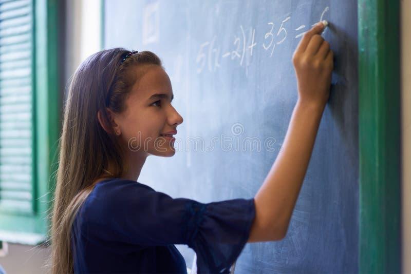 Κορίτσι που κάνει την άσκηση Math στον πίνακα στην κατηγορία γυμνασίου στοκ φωτογραφία