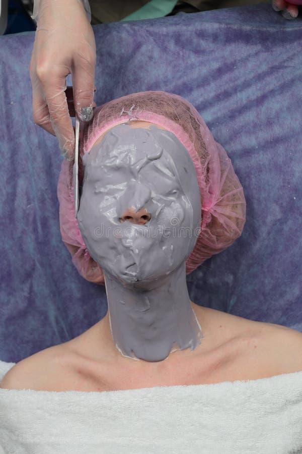 Κορίτσι που κάνει την ανύψωση με το άλας αλγινικού οξέος φλούδα-από την του προσώπου μάσκα σκονών στοκ εικόνα