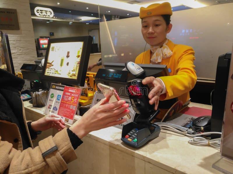 Κορίτσι που κάνει την πληρωμή σε ένα εστιατόριο μέσω κινητού στοκ εικόνες