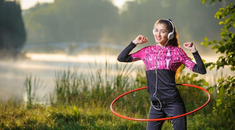 Κορίτσι που κάνει τη στεφάνη hula υπαίθρια κοντά στη λίμνη στοκ εικόνα με δικαίωμα ελεύθερης χρήσης
