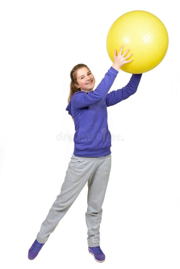 Κορίτσι που κάνει exersises στην κίτρινη σφαίρα στοκ εικόνες