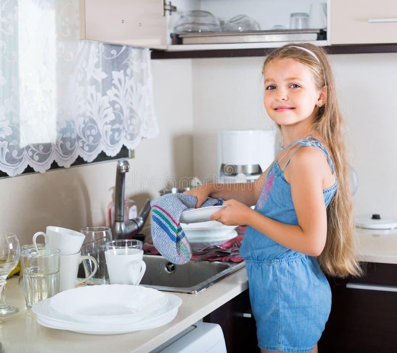 Κορίτσι που καθαρίζει dishware στο σπίτι στοκ εικόνες