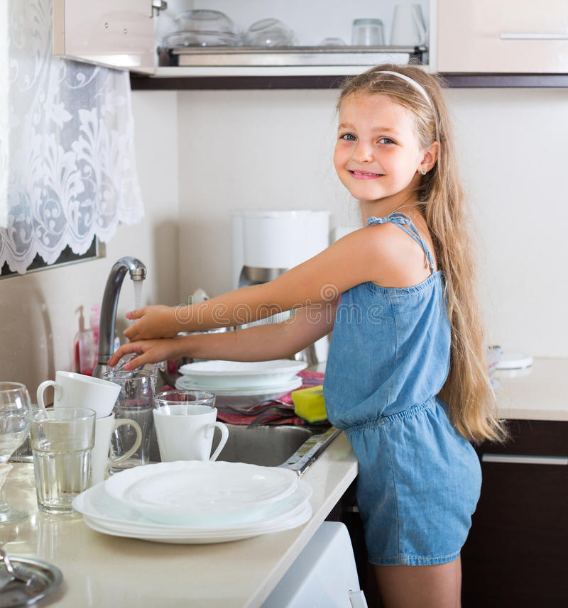 Κορίτσι που καθαρίζει dishware στο σπίτι στοκ φωτογραφίες