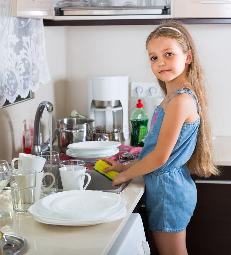 Κορίτσι που καθαρίζει dishware στο σπίτι στοκ εικόνα με δικαίωμα ελεύθερης χρήσης