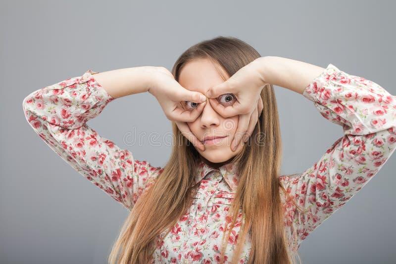 Κορίτσι που κατασκευάζει τα γυαλιά με τα δάχτυλα στοκ φωτογραφία