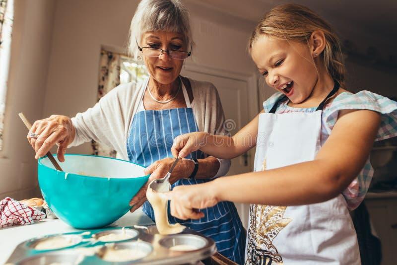 Κορίτσι που κατασκευάζει τα κέικ φλυτζανιών στοκ εικόνα