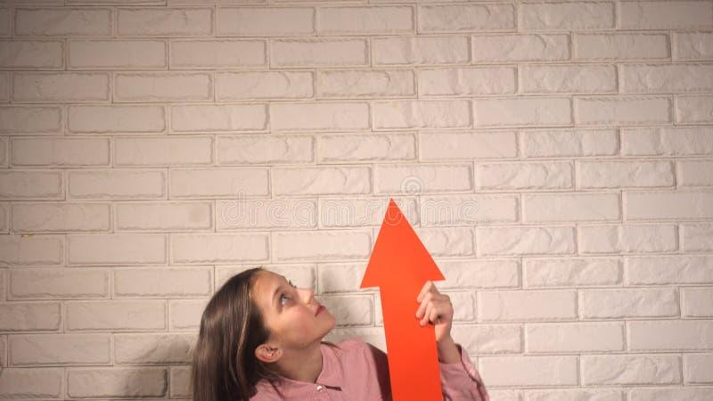 Κορίτσι που κρατά ένα έμβλημα με το κόκκινο βέλος στοκ φωτογραφία με δικαίωμα ελεύθερης χρήσης