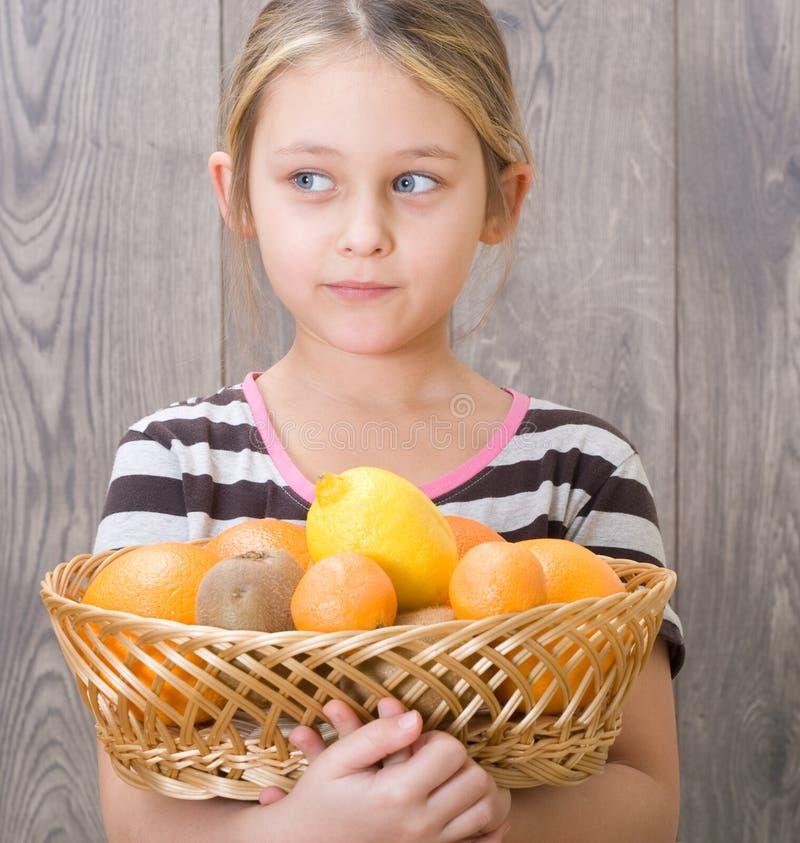 Κορίτσι που κρατά ένα καλάθι των φρούτων στοκ φωτογραφία με δικαίωμα ελεύθερης χρήσης