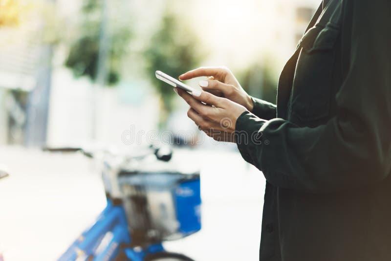 Κορίτσι που κρατά το έξυπνο τηλέφωνο στην ατμοσφαιρικά πόλη και το ποδήλατο ήλιων υποβάθρου, hipster χρησιμοποιώντας στα θηλυκά χ στοκ φωτογραφίες