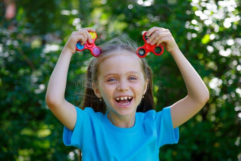 κορίτσι που κρατά το δημοφιλές fidget παιχνίδι κλωστών στοκ φωτογραφία