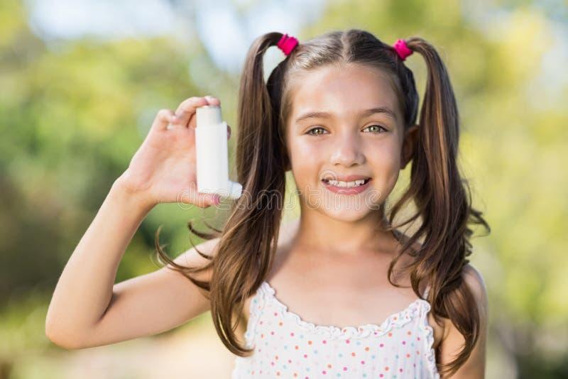 Κορίτσι που κρατά inhaler άσθματος στο πάρκο στοκ φωτογραφίες