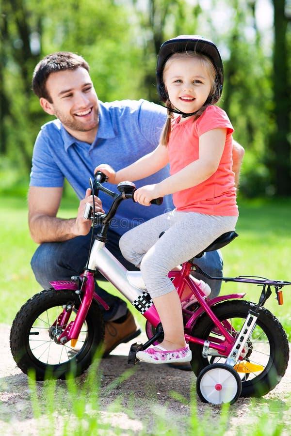 Κορίτσι που μαθαίνει να οδηγά ένα ποδήλατο με τον πατέρα της στοκ εικόνα
