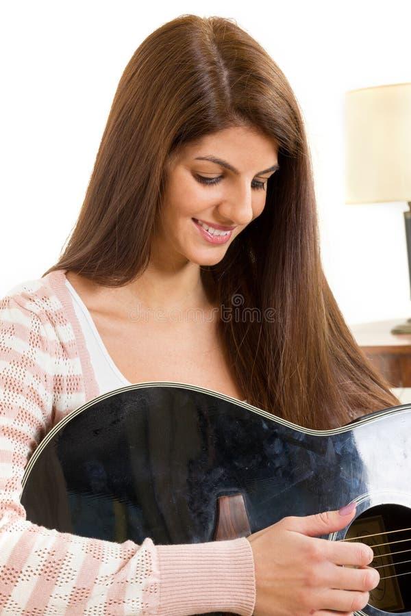 Κορίτσι που μαθαίνει να παίζει την κιθάρα στοκ εικόνα με δικαίωμα ελεύθερης χρήσης