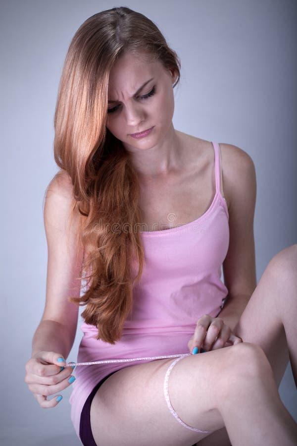 Κορίτσι που μετρά τη μέτρηση μηρών στοκ εικόνες