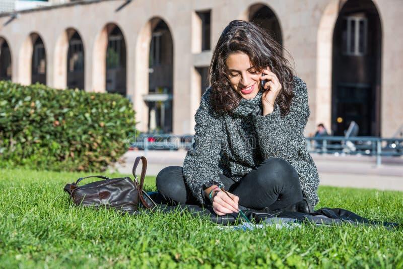 Κορίτσι που μιλά στο τηλέφωνο που χαμογελά και που κάθεται στην πράσινη χλόη στοκ φωτογραφίες με δικαίωμα ελεύθερης χρήσης
