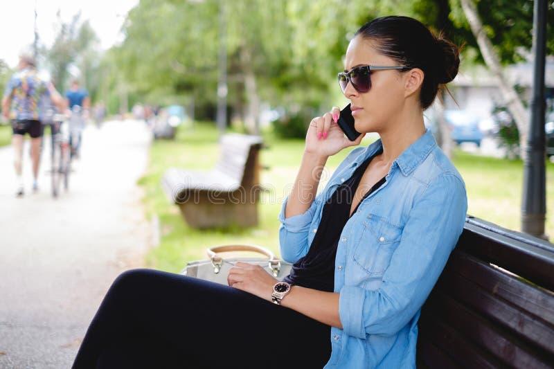Κορίτσι που μιλά στο τηλέφωνο στο πάρκο στοκ εικόνες