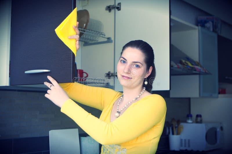 Κορίτσι που ξεσκονίζει στην κουζίνα στοκ φωτογραφίες