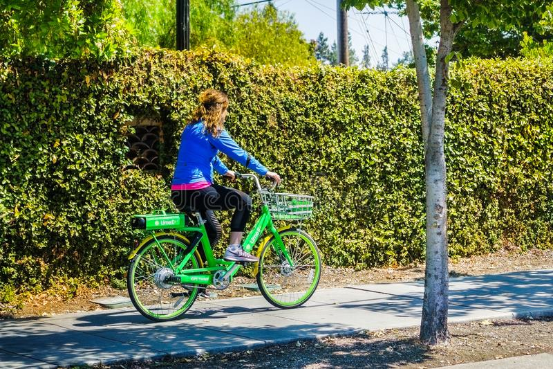 Κορίτσι που οδηγά ένα ποδήλατο ασβέστη σε ένα πεζοδρόμιο στοκ εικόνες