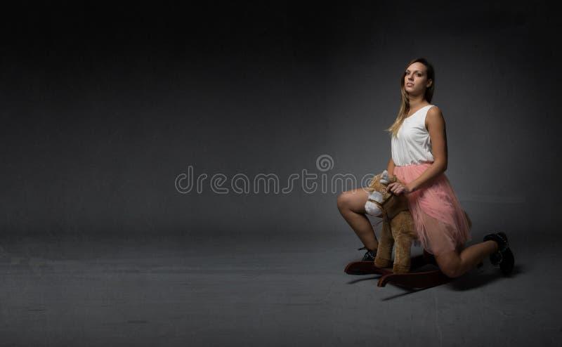 Κορίτσι που οδηγά ένα πλαστό άλογο στοκ εικόνα με δικαίωμα ελεύθερης χρήσης