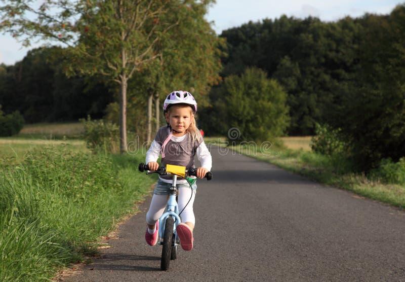 Κορίτσι που οδηγά το ποδήλατο κατάρτισής της στοκ εικόνα