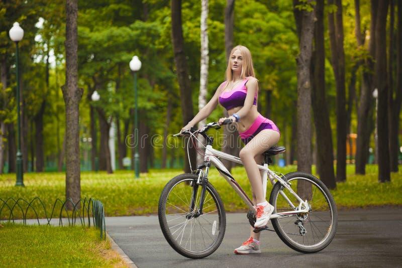 Κορίτσι που οδηγά το ποδήλατό της σε μια ηλιόλουστη ημέρα στοκ φωτογραφίες